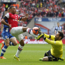 Wigan Athletic's goalkeeper Scott Carson, right, stops a shot from Arsenal's Alex Oxlade-Chamberlain during their English FA Cup semifinal soccer match at Wembley Stadium in London, Saturday, April 12, 2014