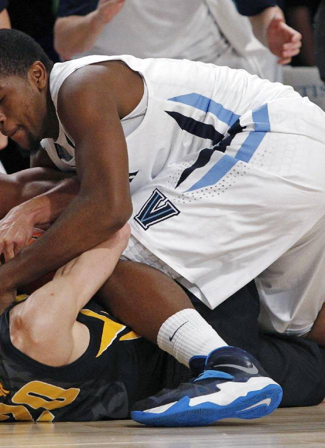 Iowa's Jarrod Uthoff, center, and Villanova's Josh Hart, left, and Kris Jenkins scramble for possession of a loose ball during the second half of an NCAA college basketball game in Paradise Island, Bahamas, Saturday, Nov. 30, 2013. Villanova defeated No. 23 Iowa 88-83 in overtime to claim the Battle 4 Atlantis championship