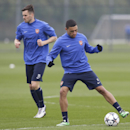 Arsenal's Alex Oxlade-Chamberlain, right, controls the ball alongside Carl Jenkinson during a training session at their London Colney training ground, Monday, March 10, 2014. Arsenal will play in a Champions League last sixteen second leg soccer match aga