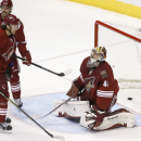 Martin Hanzal (11), of the Czech Republic, skates past goalie Mike Smith (41) after Hanzal knocked the puck past his own goalie as Coyotes' David Schlemko, back left, skates in from behind during overtime of an NHL hockey game Tuesday, Nov. 25, 2014, in G