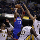 Philadelphia 76ers forward Evan Turner (12) shoots over Indiana Pacers defenders Paul George (24), Roy Hibbert (55) and Luis Scola (4) during the first half of an NBA basketball game in Indianapolis, Saturday, Nov. 23, 2013 The Associated Press