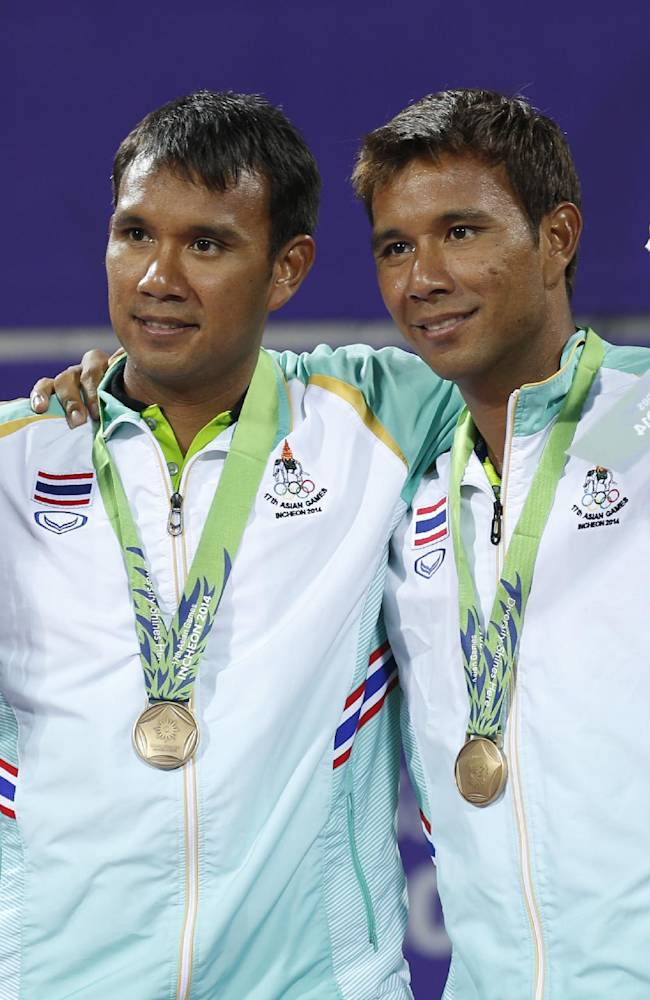 Bronze medal winners Sanchai Ratiwatana, right, and Sonchat Ratiwatana celebrate after winning the men's doubles tennis match at the 17th Asian Games in Incheon, South Korea, Monday, Sept. 29, 2014