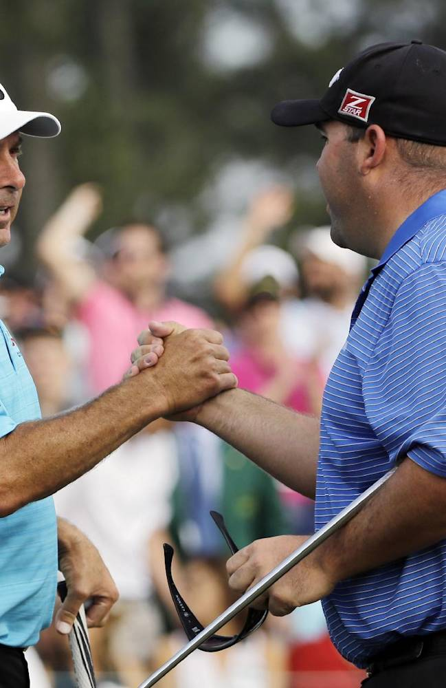 Fred Couples, left, shakes hands with Kevin Stadler on the 18th green following their fourth round of the Masters golf tournament Sunday, April 13, 2014, in Augusta, Ga