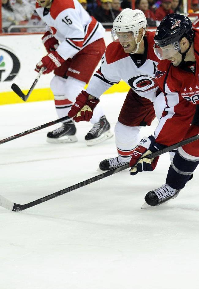 Washington Capitals right wing Troy Brouwer (20) battles for the puck against Carolina Hurricanes center Jordan Staal (11) during the second period of an NHL hockey game, Thursday, Jan. 2, 2014, in Washington
