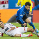 Montreal Impact's Felipe Martins, right, and New England Revolution's Kelyn Rowe battle for the ball during the second half of an MLS soccer game in Montreal, Saturday, Oct. 11, 2014 The Associated Press