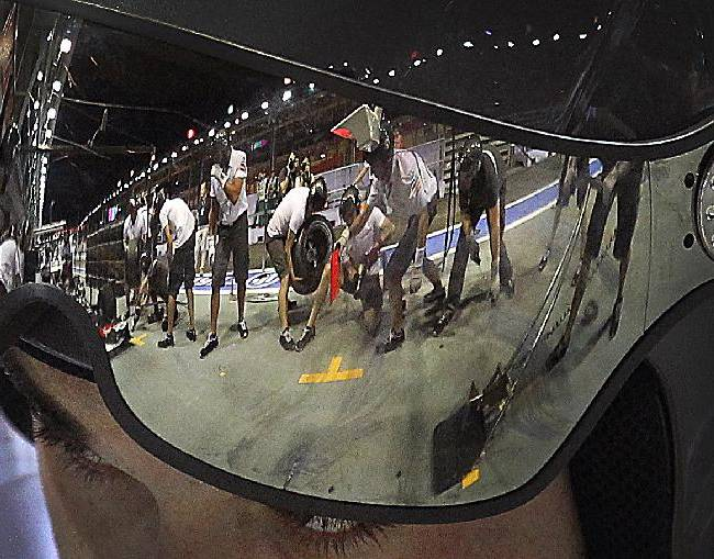 The Sauber team mechanics are reflected on a visor worn by one of them during their practice session to change tires at the pit area Thursday, Sept. 19, 2013, in Singapore, ahead of Sunday's Formula One Grand Prix in Singapore