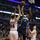 Orlando Magic guard Doron Lamb (1) shoots between Chicago Bulls forward Mike Dunleavy (34) and guard Jimmer Fredette, right, during the first half of an NBA basketball game Monday, April 14, 2014, in Chicago The Associated Press