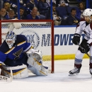 St. Louis Blues goalie Brian Elliott makes a save as Colorado Avalanche's Maxime Talbot, right, waits in front of the net for the rebound during the second period of an NHL hockey game Monday, Jan. 19, 2015, in St. Louis The Associated Press