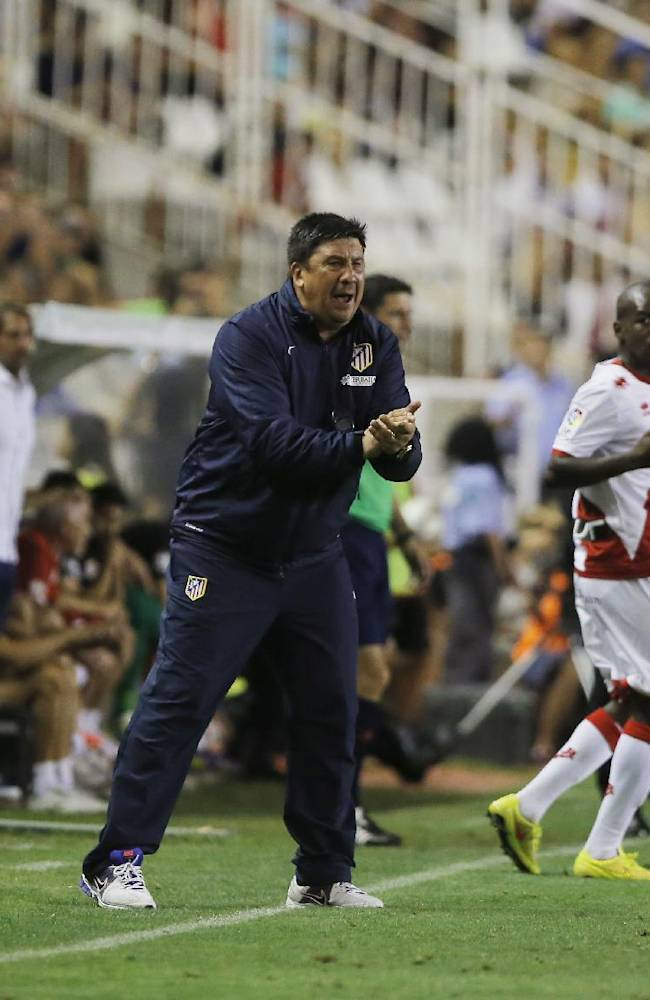 Atletico's coach assistant German Burgos, center, shouts during a Spanish La Liga soccer match between Rayo Vallecano and Atletico Madrid at the Vallecas stadium in Madrid, Spain, Monday, Aug. 25, 2014