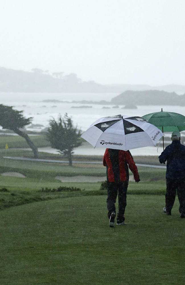 From left, Mike Weir of Canada and amateur playing partners George Roberts and Charles Schwab walk down to the 11th green of the Monterey Peninsula Country Club during the first round of the AT&T Pebble Beach Pro-Am golf tournament Thursday, Feb. 6, 2014, in Pebble Beach, Calif. Play was suspended because of steady rain