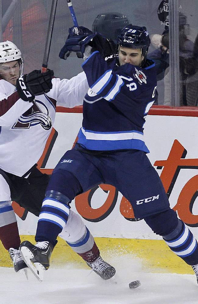 Colorado Avalanche's Paul Carey (28) and Winnipeg Jets' Patrice Cormier (28) fight for the puck during the first period of an NHL hockey game Wednesday, March 19, 2014, in Winnipeg, Manitoba