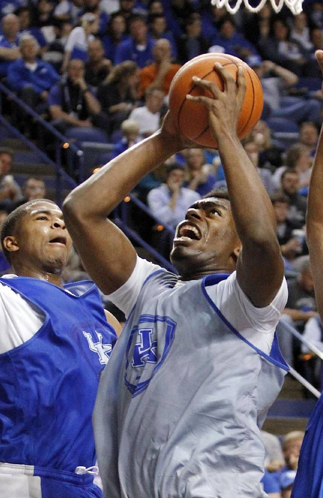 White team's Dakari Johnson, middle, shoots between Blue team's Aaron Harrison, left, and Marcus Lee during Kentucky's NCAA college basketball scrimmage, Tuesday, Oct. 29, 2013, in Lexington, Ky. The Blue team won 99-71