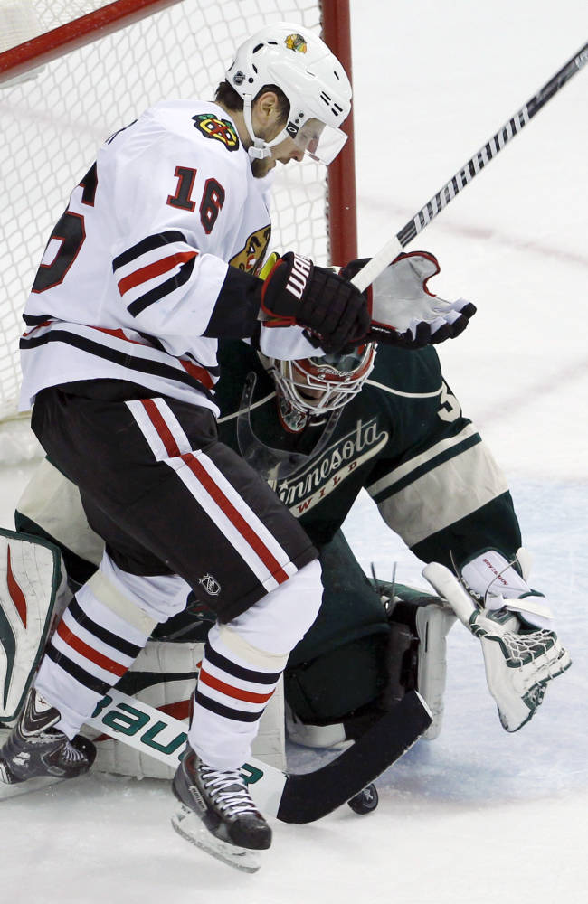 Minnesota Wild goalie Ilya Bryzgalov, right, of Russia, covers the puck in front of Chicago Blackhawks center Marcus Kruger (16) during the first period of Game 3 of an NHL hockey second-round playoff series in St. Paul, Minn., Tuesday, May 6, 2014