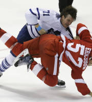 Toronto Maple Leafs right wing David Clarkson (71) takes down Detroit Red Wings defenseman Jonathan Ericsson (52) of Sweden during the third period of an NHL hockey game in Detroit, Friday, Sept. 27, 2013. (AP Photo/Carlos Osorio)