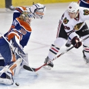 Chicago Blackhawks' Ben Smith (28) is stopped by Edmonton Oilers goalie Ben Scrivens (30) during the third period of an NHL hockey game Friday, Jan. 9, 2015, in Edmonton, Alberta The Associated Press