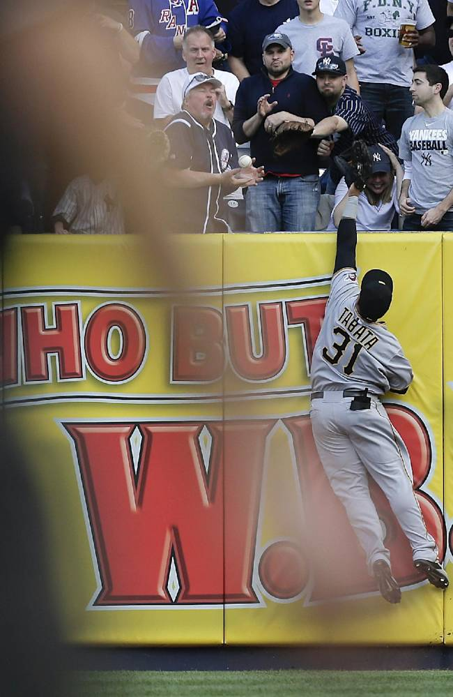 Pittsburgh Pirates right fielder Jose Tabata leaps unsuccessfully for a home run hit by New York Yankees first baseman Mark Teixeira as the ball slips through a fan's hands during the first inning a baseball game, Saturday, May 17, 2014, in New York