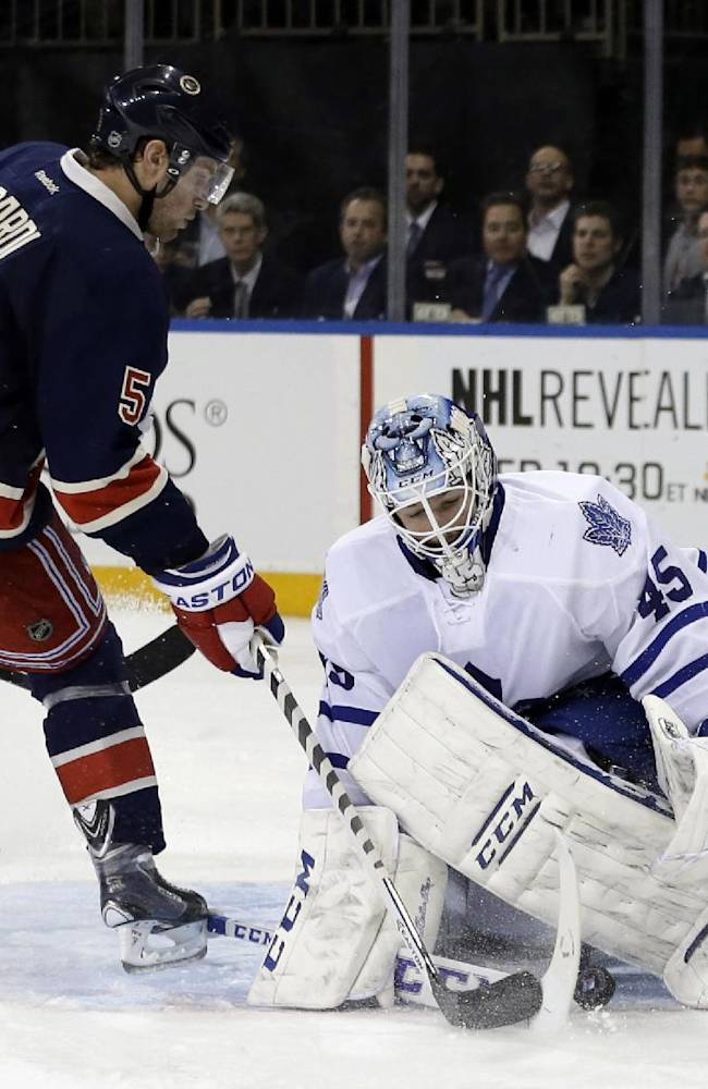 Toronto Maple Leafs goalie Jonathan Bernier (45) stops a shot by New York Rangers' Dan Girardi (5) during the second period of an NHL hockey game Wednesday, March 5, 2014, in New York