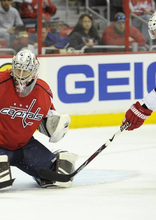 Washington Capitals goalie Philipp Grubauer (31)reaches for the puck against Carolina Hurricanes left wing Tuomo Ruutu (15), of Finland, during the second period of an NHL hockey game, Thursday, Jan. 2, 2014, in Washington