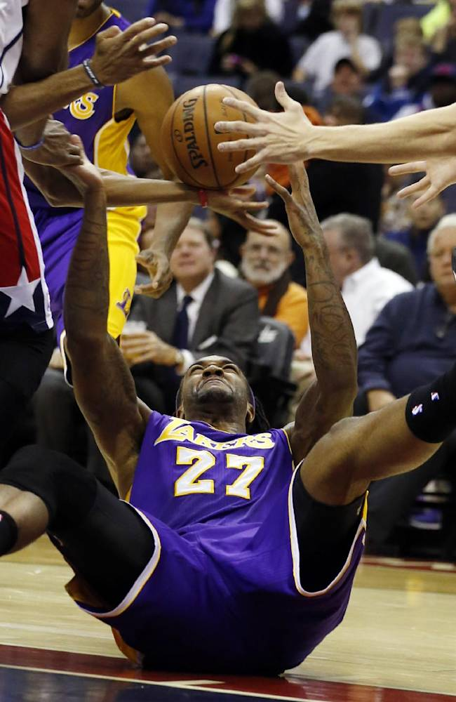 Los Angeles Lakers center Jordan Hill (27) reaches from the floor for a loose ball in the first half of an NBA basketball game against the Washington Wizards Tuesday, Nov. 26, 2013, in Washington