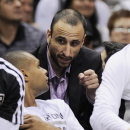 San Antonio Spurs guard Manu Ginobili, rear, of Argentina, talks to Spurs' Patty Mills, of Australia, during the first half of an NBA basketball game against the Phoenix Suns on Friday, April 11, 2014, in San Antonio The Associated Press