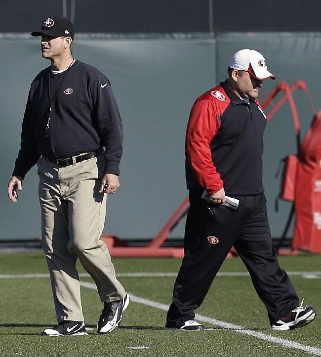 San Francisco 49ers coach Jim Harbaugh, left, and offensive coordinator Greg Roman walk on the field during NFL football practice in Santa Clara, Calif., Wednesday, Jan. 15, 2014. The 49ers are scheduled to play the Seattle Seahawks for the NFC championship on Sunday