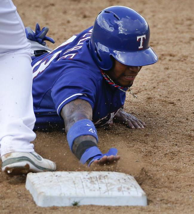 Texas Rangers' Engel Beltre gets back safely to first base while playing the Oakland Athletics during the fifth inning of a spring training baseball game Saturday, March 1, 2014, in Phoenix