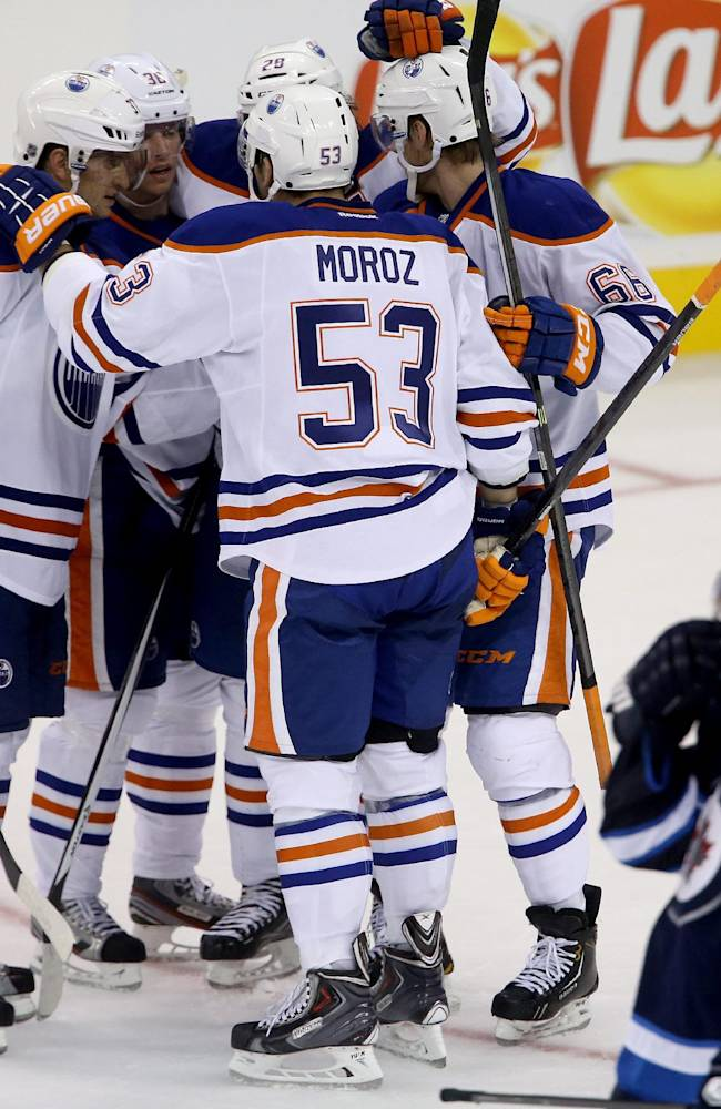 Edmonton Oilers players celebrate after Mitchell Moroz (53) scored against Winnipeg Jets goaltender Ondrej Pavelec, not seen, during the third period of a preseason NHL hockey game in Winnipeg, Manitoba, Tuesday, Sept. 17, 2013