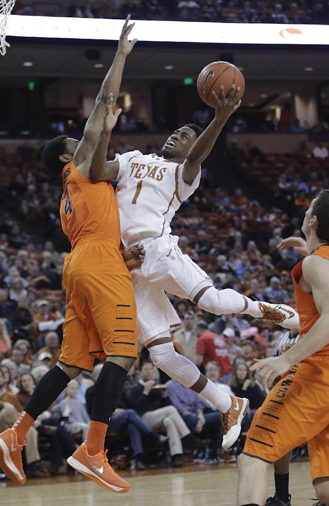 Texas' Isaiah Taylor (1) drives against Oklahoma State's Brian Williams during the first half on an NCAA college basketball game, Tuesday,  Feb. 11, 2014, in Austin, Texas