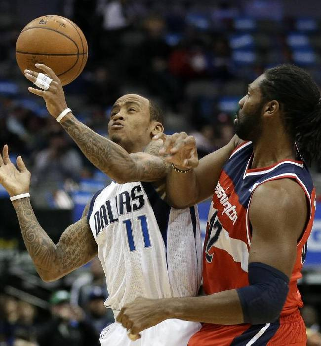 Dallas Mavericks' Monta Ellis (11) temporarily loses control of the ball after colliding with Washington Wizards' Nene Hilario (42), of Brazil, at mid-court in the first half of an NBA basketball game, Tuesday, Nov. 12, 2013, in Dallas