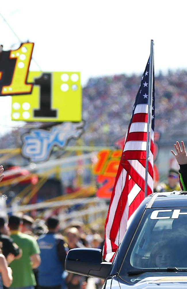 Danica Patrick, right, waves to fans as she rides in a truck to her car for the NASCAR Sprint Cup Series auto race at Talladega Superspeedway, Sunday, Oct. 19, 2014, in Talladega, Ala