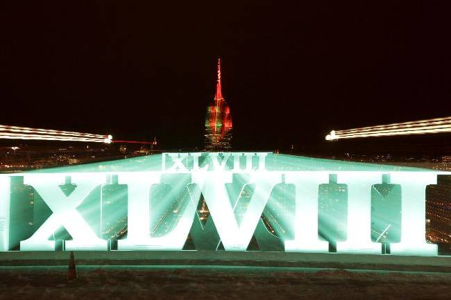 In this photograph taken with a zoom lens and a long exposure, a sign for NFL football's Super Bowl XLVIII stands at Pier A Park in Hoboken, N.J., Tuesday, Jan. 28, 2014, with the Empire State Building in New York in the background. The Seattle Seahawks and the Denver Broncos are scheduled to play on Sunday in East Rutherford, N.J