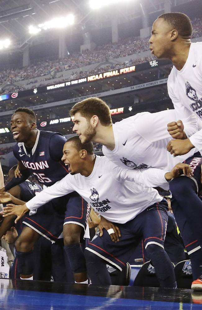 Connecticut players celebrate against Florida in the final moments of the NCAA Final Four tournament college basketball semifinal game Saturday, April 5, 2014, in Arlington, Texas. Connecticut won 63-53
