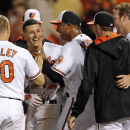 Baltimore Orioles' Manny Machado, second from left, celebrates with teammates after hitting a game-winning solo home run in the 12th inning of a baseball game against the Los Angeles Angels, Tuesday, July 29, 2014, in Baltimore. Baltimore won 7-6. (AP Photo/Patrick Semansky)