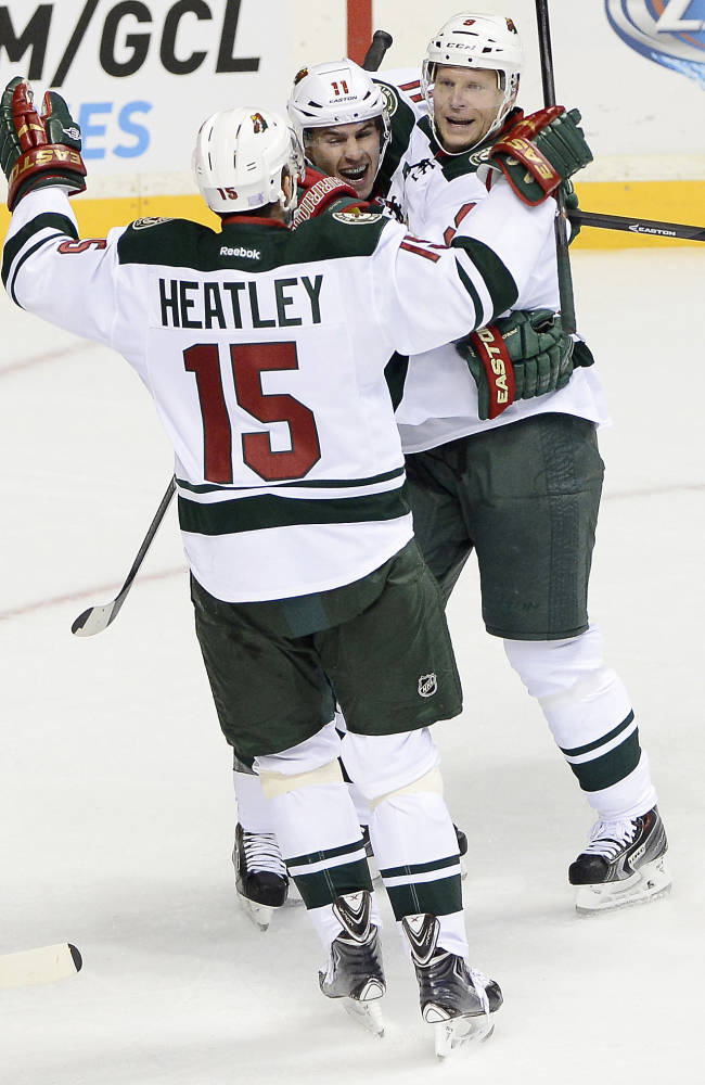 Minnesota Wild left wing Zach Parise, center, celebrates with Dany Heatley (15) and Mikko Koivu, right, after scoring a goal against Nashville in the first period of an NHL hockey game on Tuesday, Oct. 8, 2013, in Nashville, Tenn