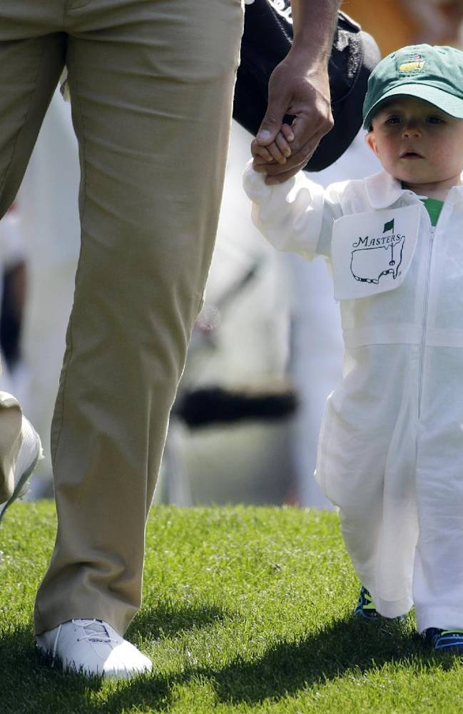 Scott Stallings walks with his son Finn after teeing off on the first hole during the par three competition at the Masters golf tournament Wednesday, April 9, 2014, in Augusta, Ga