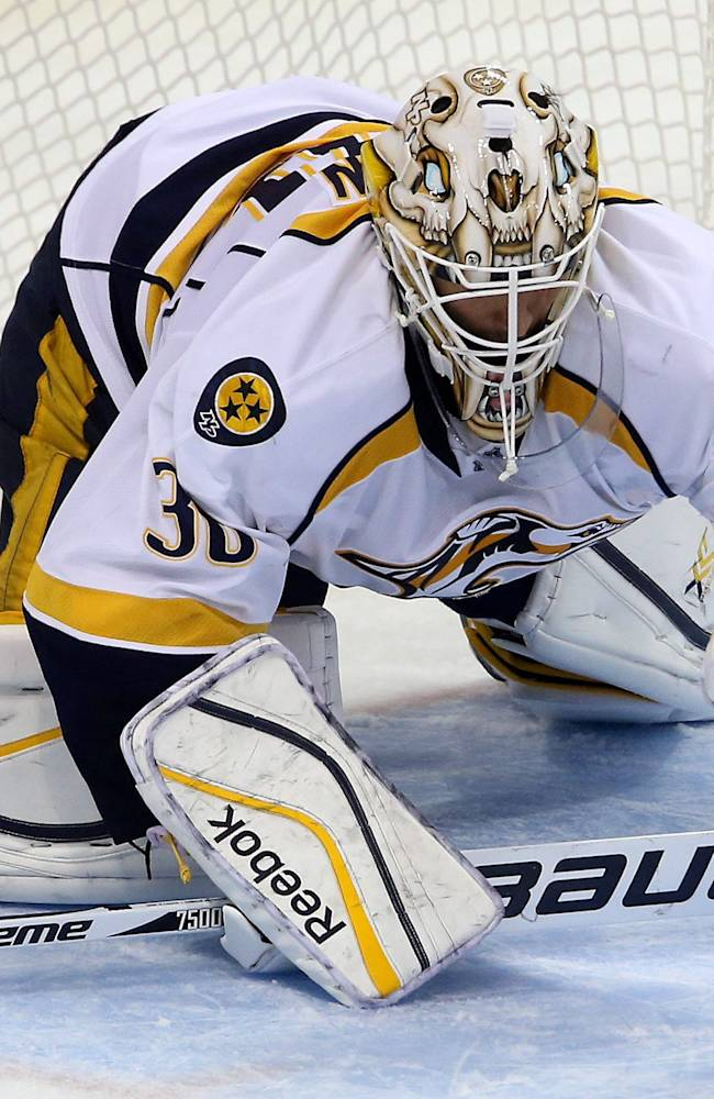 Nashville Predators' goaltender Carter Hutton (30) covers a bouncing puck during third period NHL hockey action in Winnipeg, Manitoba, Sunday, Oct. 20, 2013