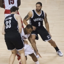 Toronto Raptors guard Kyle Lowry, center, works between Brooklyn Nets' Mirza Teletovic (33) and Deron Williams (8) during the first half of Game 2 in an NBA basketball first-round playoff series, Tuesday, April 22, 2014, in Toronto The Associated Press