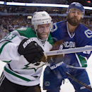 Vancouver Canucks' Dan Hamhuis, right, checks Dallas Stars' Alex Goligoski during the first period of an NHL hockey game in Vancouver, British Columbia, on Wednesday, Dec. 17, 2014 The Associated Press