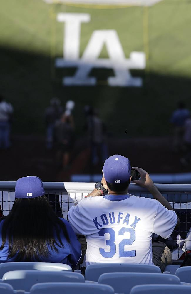 A fan takes pictures as the Los Angeles Dodgers take batting practice before Game 4 of the National League baseball championship series against the St. Louis Cardinals, Tuesday, Oct. 15, 2013, in Los Angeles