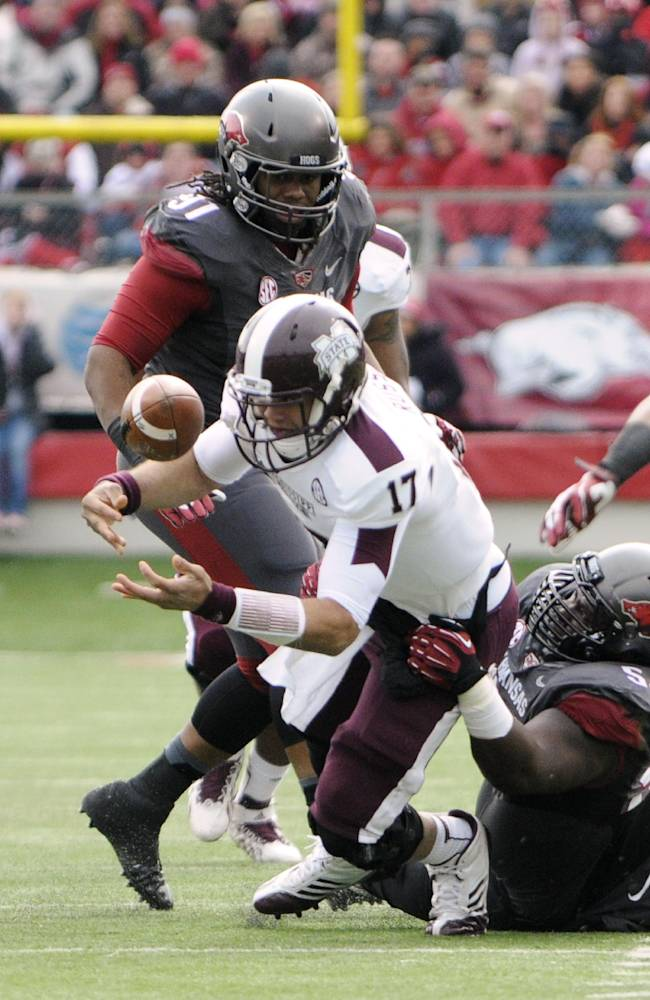 Mississippi State quarterback Tyler Russell (17) recovers his own fumble after being tackled by Arkansas defensive tackle Byran Jones, right, as defensive tackle Darius Philon (91) participates in the first half of an NCAA college football game in Little Rock, Ark., Saturday, Nov. 23, 2013