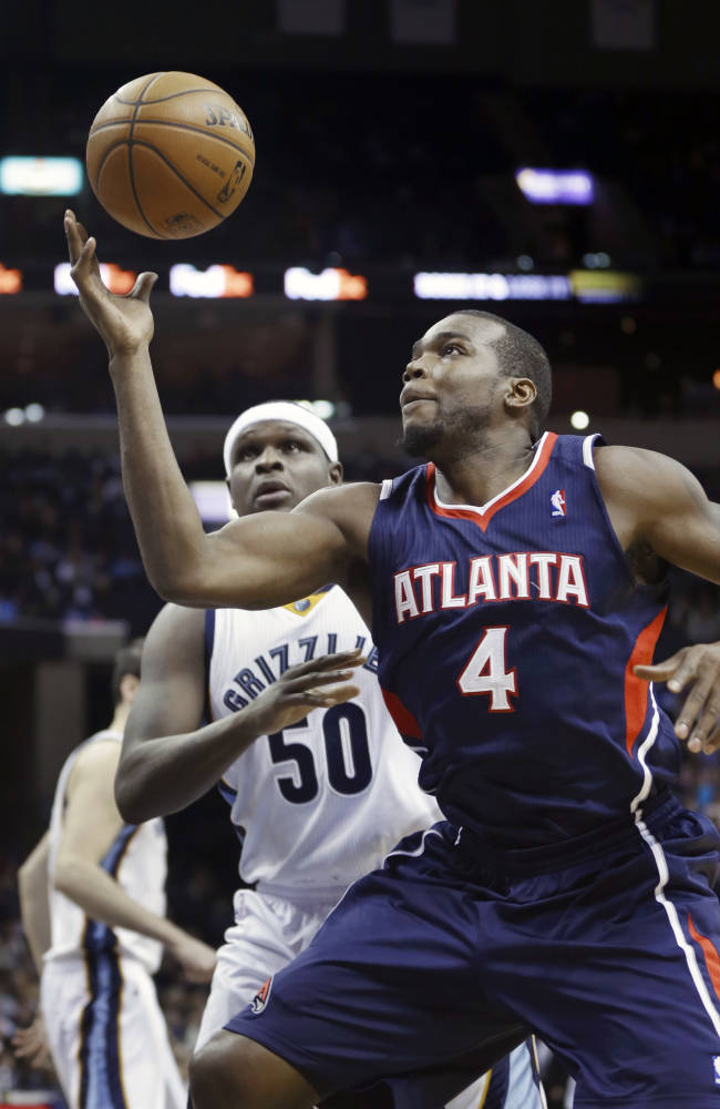 Atlanta Hawks' Paul Millsap (4) grabs a pass in front of Memphis Grizzlies' Zach Randolph (50) in the first half of an NBA basketball game in Memphis, Tenn., Sunday, Jan. 12, 2014