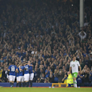 Everton's Leighton Baines, obscured, is engulfed by teammates after scoring a penalty against Wolfsburg during their Europa League Group H soccer match at Goodison Park Stadium, Liverpool, England, Thursday Sept. 18, 2014