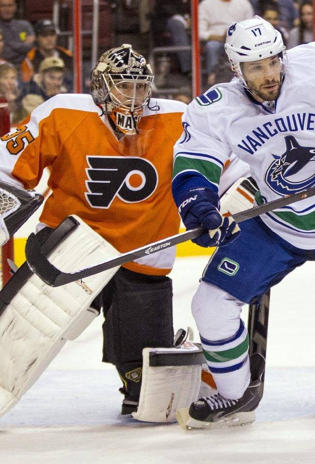 Vancouver Canucks' Ryan Kesler, right, skates in front of Philadelphia Flyers goalie Steve Mason, left, during the first period of an NHL hockey game, Tuesday, Oct. 15, 2013, in Philadelphia