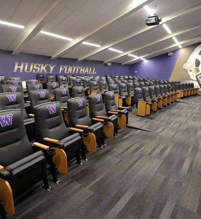 In this Aug. 28, 2013 file photo, padded chairs line a meeting room for offensive players in the football operations center at the newly renovated Husky Stadium on the campus of the University of Washington in Seattle. Call them football palaces, and no college football program can call itself big-time without one that will leave recruits wide-eyed