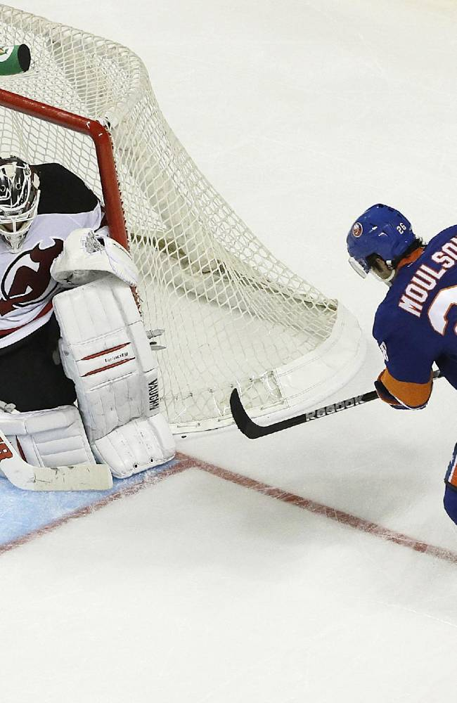 New Jersey Devils goalie Cory Schneider, left, makes a save on a shot by New York Islanders left wing Matt Moulson (26) during the third period of a preseason NHL hockey game, Saturday, Sept. 21, 2013, in New York. The Devils won 3-0
