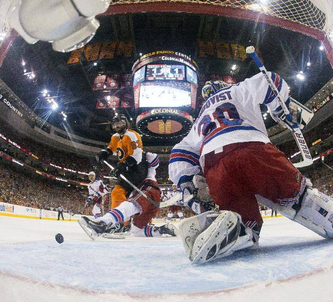 In this photo taken with a fisheye lens, Philadelphia Flyers' Jakub Voracek, left, of the Czech Republic, scores a goal against New York Rangers' Henrik Lundqvist, right, of Sweden, with Rangers' Marc Staal, center, during the second period in Game 4 of an NHL hockey first-round playoff series on Friday, April 25, 2014, in Philadelphia. The Flyers won 2-1