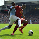 Liverpool's Glen Johnson right, is tackled by Manchester City's Fernandinho during their English Premier League soccer match at Anfield in Liverpool, England, Sunday April. 13, 2014