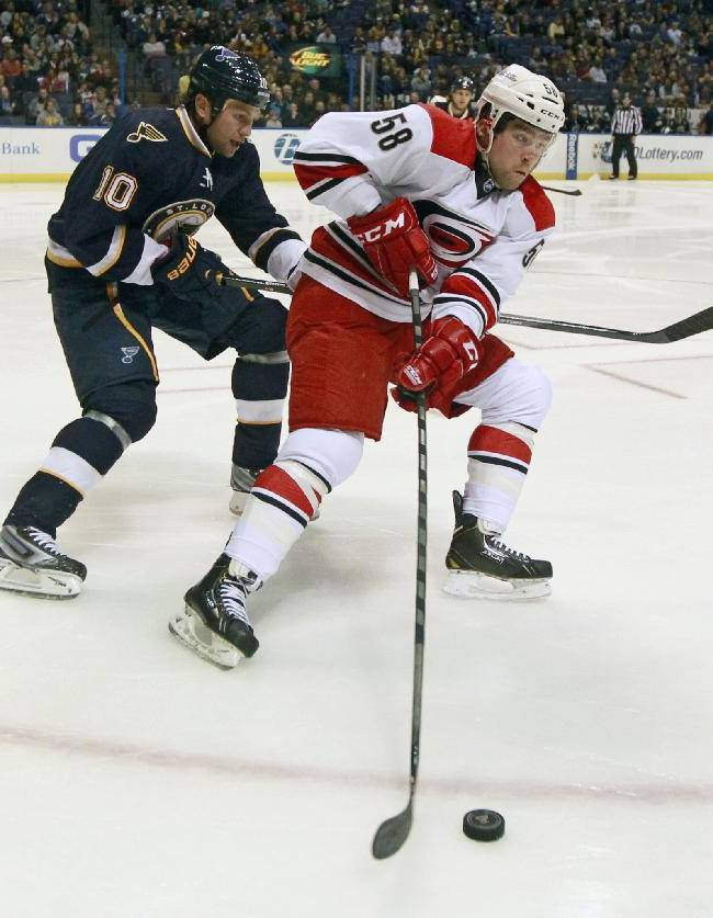 Carolina Hurricanes' Chris Terry, right, controls the puck as St. Louis Blues' Brenden Morrow gives chase during the first period of an NHL hockey game Saturday, Nov. 16, 2013, in St. Louis