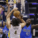 Indiana Pacers forward Luis Scola (4) is fouled as he shoots over Dallas Mavericks guard Vince Carter, left, and center DeJuan Blair during the first half of an NBA basketball game in Indianapolis, Wednesday, Feb. 12, 2014 The Associated Press