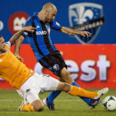 Montreal Impact's Marco Di Vaio, right, and Houston Dynamo's Eric Brunner battle for the ball during the second half of an MLS soccer game in Montreal, Saturday, Aug. 24, 2013. (AP Photo/The Canadian Press, Graham Hughes)